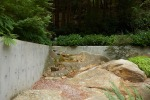 the creek/van damm residence - concrete wall integrated into boulders